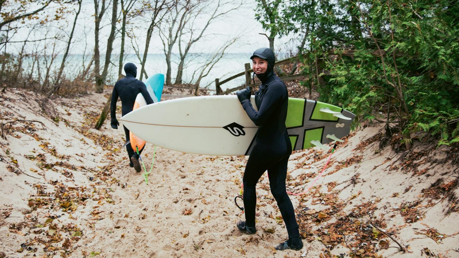 Dos surfistas en trajes de neopreno caminando por un sendero arenoso hacia el lago Michigan.