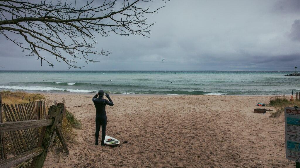 Un surfista en un traje de neopreno parado en la playa del lago Michigan mirando al agua y el cielo gris.