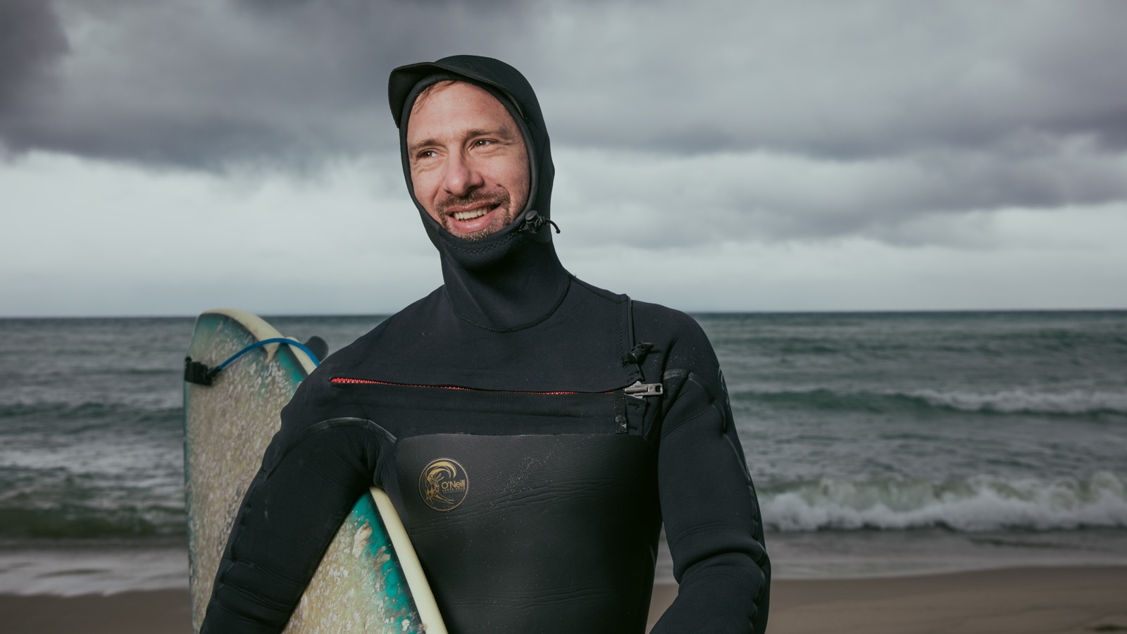 Un surfista con todo el equipo sostiene su tabla de surf en la playa del lago Michigan con las olas rompiendo detrás de él.