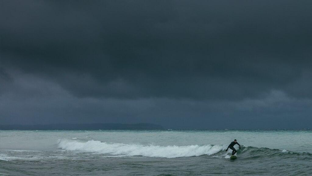 Un surfistaatraviesauna ola en las oscuras aguas del lago Michigan con un inquietante cielo gris detrás de él.