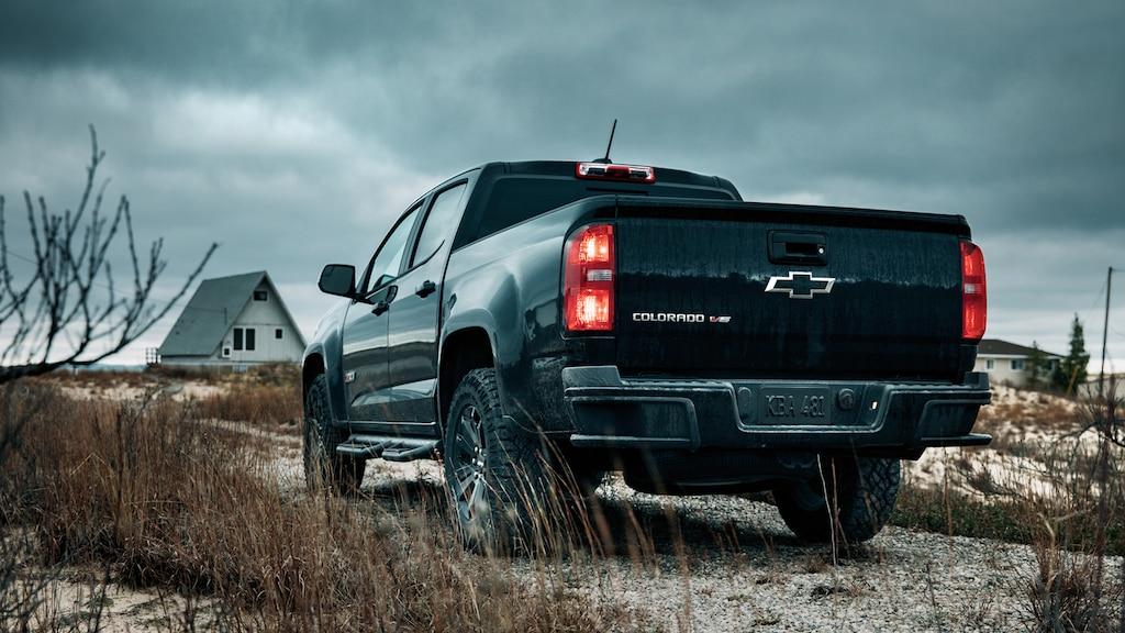 La parte trasera de una Chevy Colorado Z71 2018 de cabina extendida con Midnight Edition color Negro sobre la grava cerca de la playa del lago Michigan.