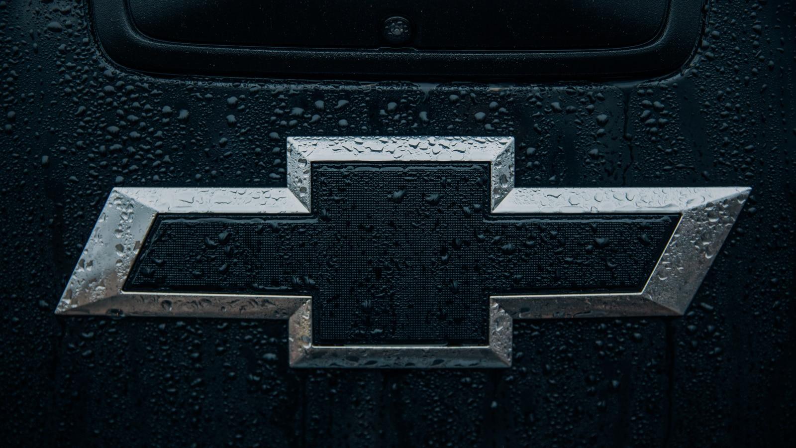 El logo de corbatín color Negro y Plateado de Chevrolet salpicado de lluvia en la parte trasera de la Colorado Z71 de cabina extendida con Midnight Edition.