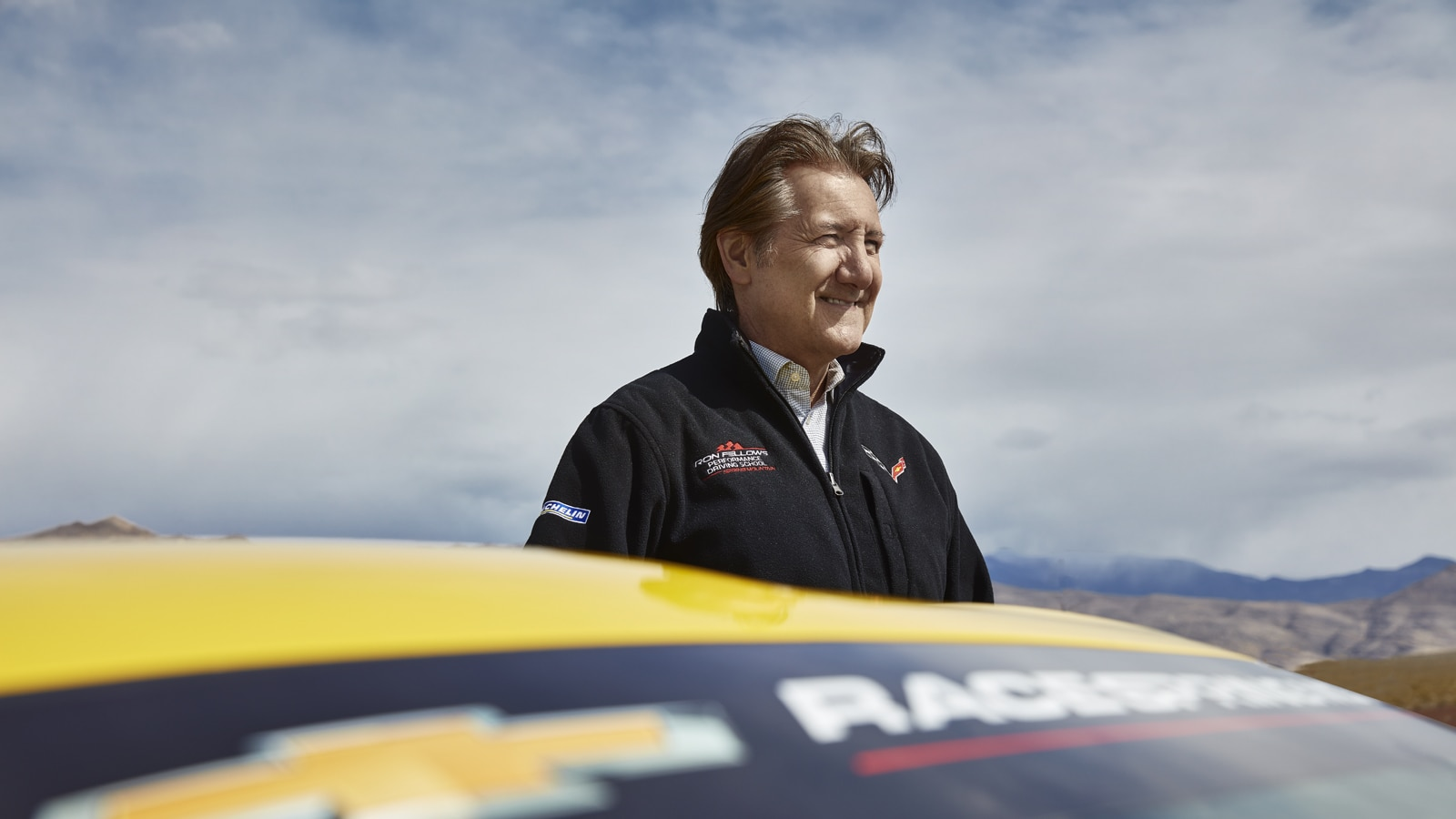 Ron Fellows detrás de un Corvette amarillo.