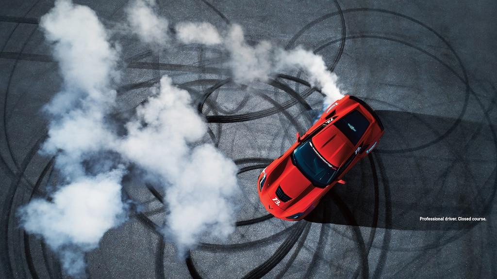 Toma cenital de un Corvette rojo haciendo giros en una pista cerrada.