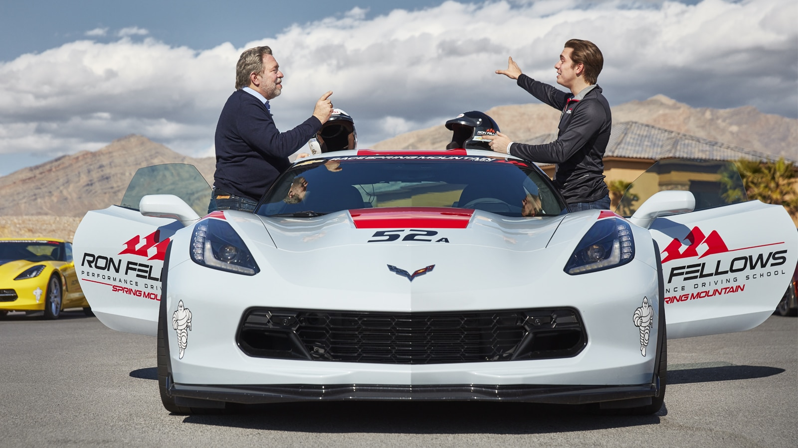 Estudiantes de pie y conversando a ambos lados de un Corvette blanco.