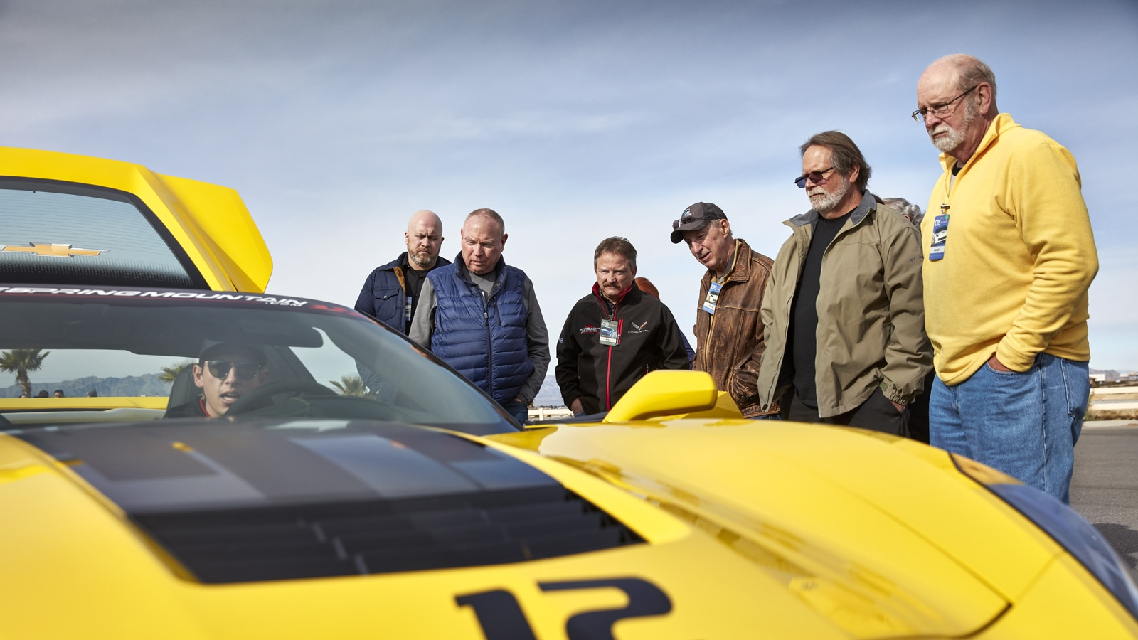 Estudiantes admirando un Corvette amarillo.