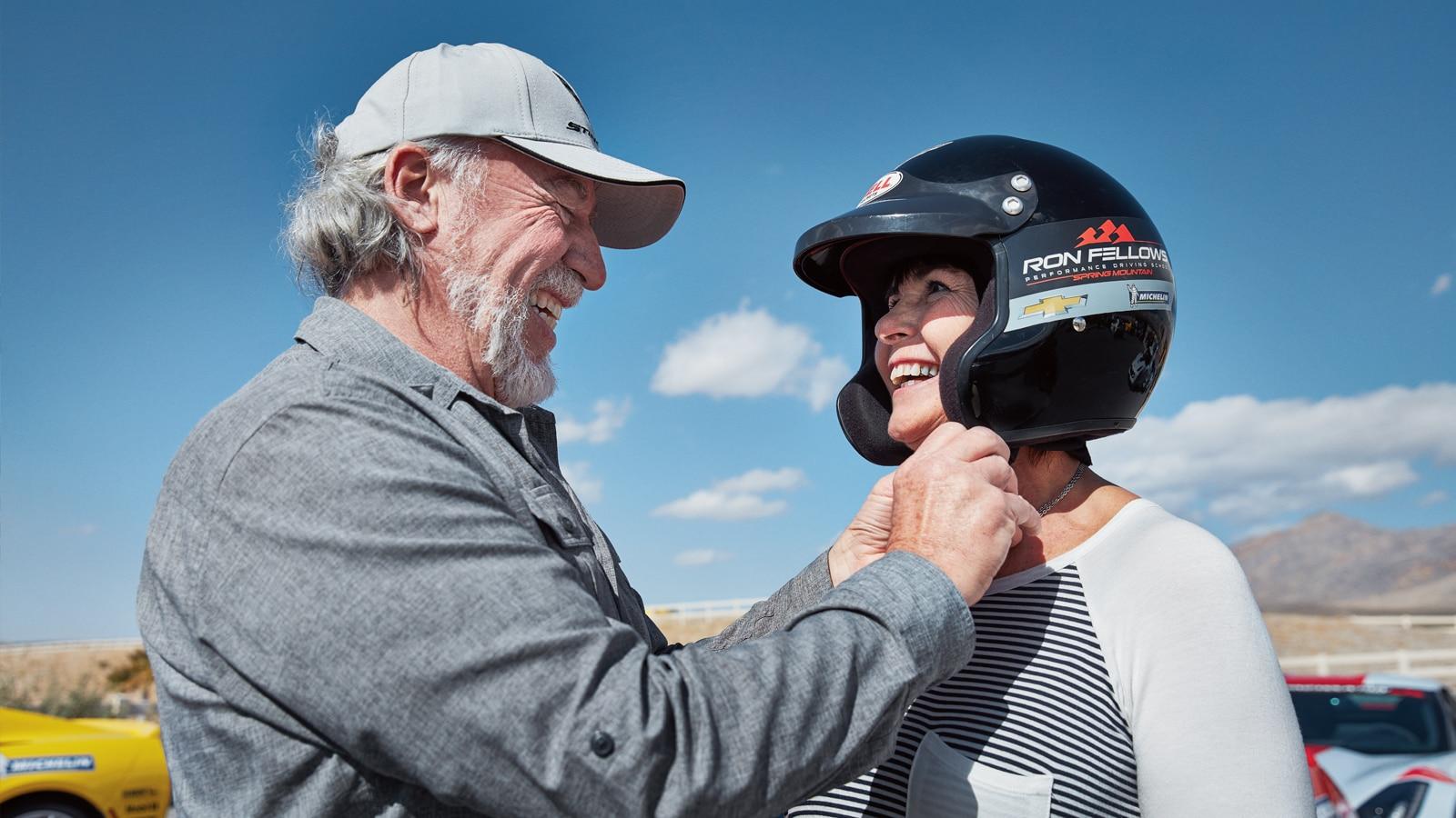 Un hombre ayuda a una estudiante a ajustarse el casco.