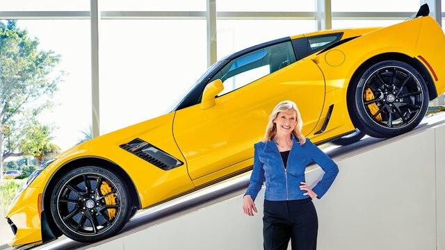 Directora ejecutiva de Hertz, Kathy Marinello, con un Chevrolet Corvette amarillo exhibido en una rampa detrás suyo.