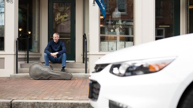 Mike Lucey sentado en un banco con el estuche de su guitarra con su Chevrolet Malibu en primer plano.