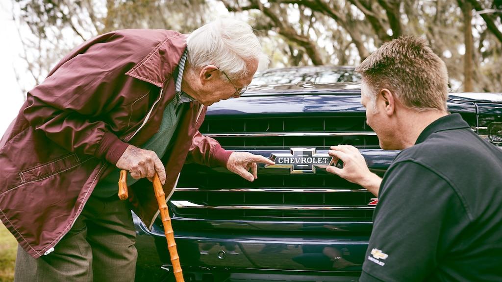 Paul Hitch y Eric Stanczak de pie admirando el corbatín tradicional en la parrilla de la Chevy Silverado Centennial Edition.