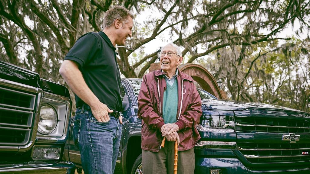 Eric Stanczak y Paul Hitch están parados hablando entre dos camionetas Chevy.