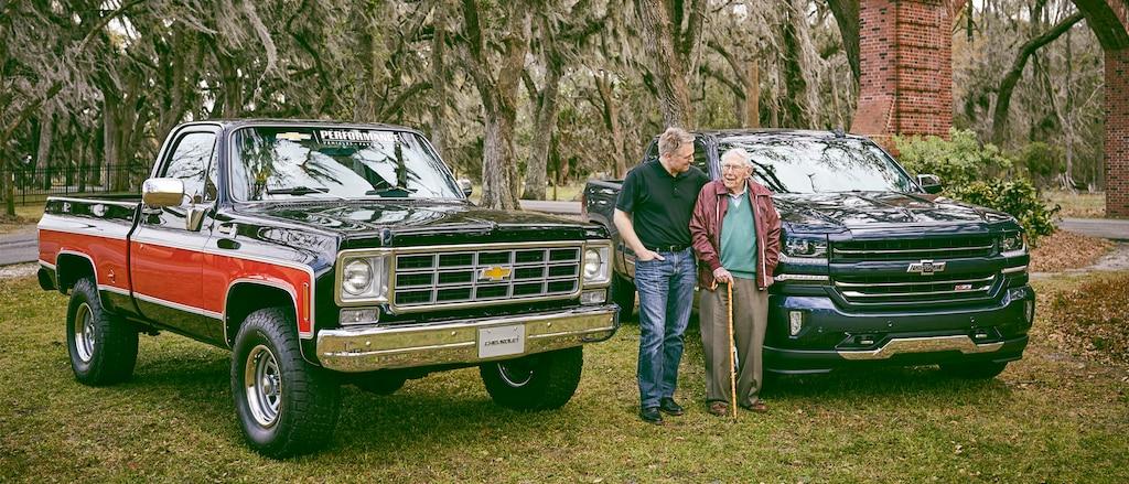Eric Stanczak y Paul Hitch están parados hablando entre una camioneta Chevy clásica y una Chevy Silverado Centennial Edition.
