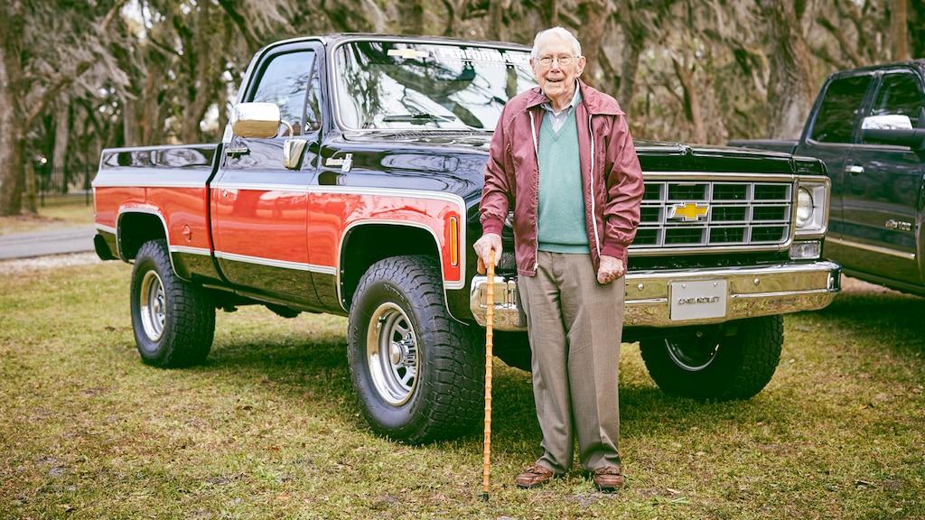 Paul Hitch está parado frente a una camioneta pickup Chevy de la era 70 que él y su equipo ayudaron a diseñar.