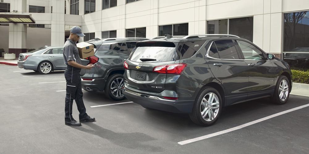 Entrega de un paquete en la cajuela de un vehículo Chevrolet.