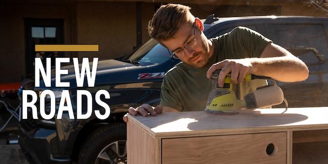 Un hombre lija un proyecto de carpintería con una Chevy Silverado 2019 en el fondo.