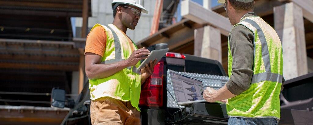 Dos trabajadores comerciales hablando cerca de una Chevy Silverado