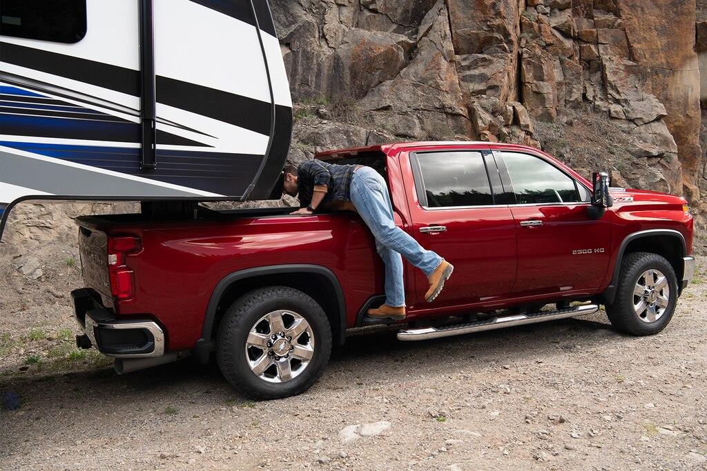 Un hombre usa el escalón lateral exterior de la totalmente nueva camioneta Chevy Silverado HD 2020 para llegar más fácil al almacenamiento de la caja
